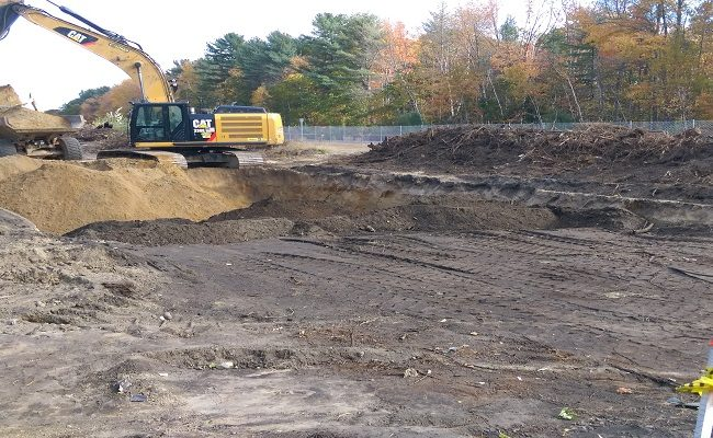 photo of an excavator moving dirt at a construction site