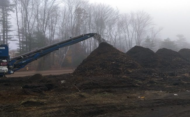 photo of construction equipment pilling up dirt into piles