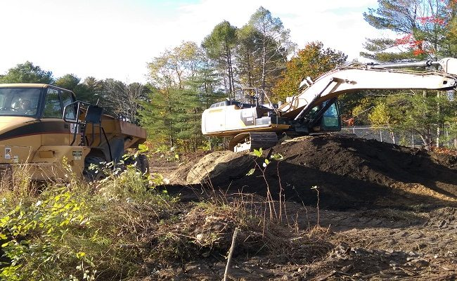 photo of an excavator and construction truck