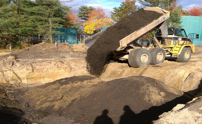 photo of a construction truck dumping dirt into a hole