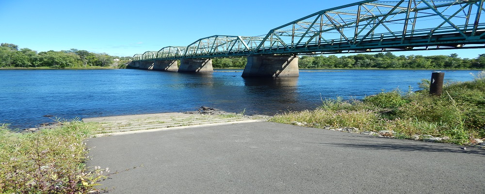 photo of a boat landing next to a bridge over a river