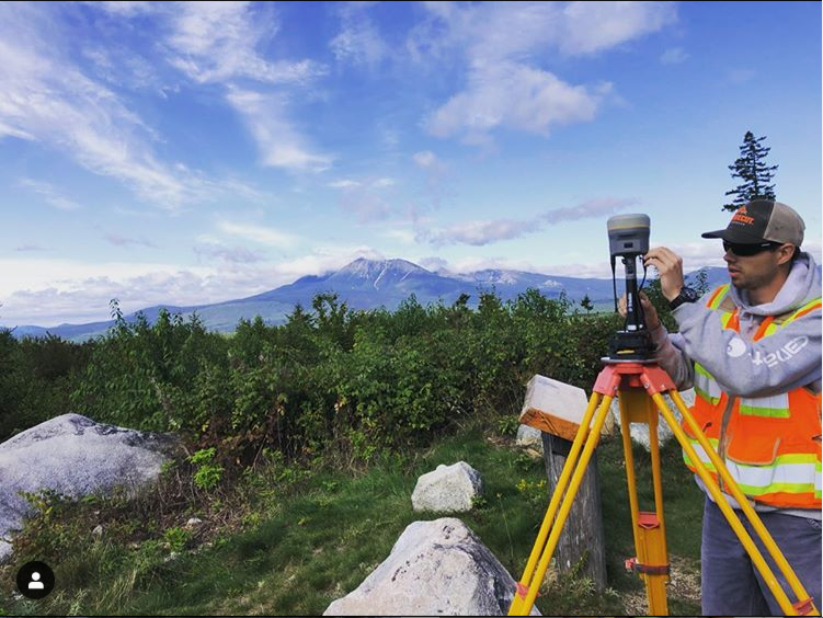 photo of an engineer using surveying equipment on a mountain with a mountain in the background