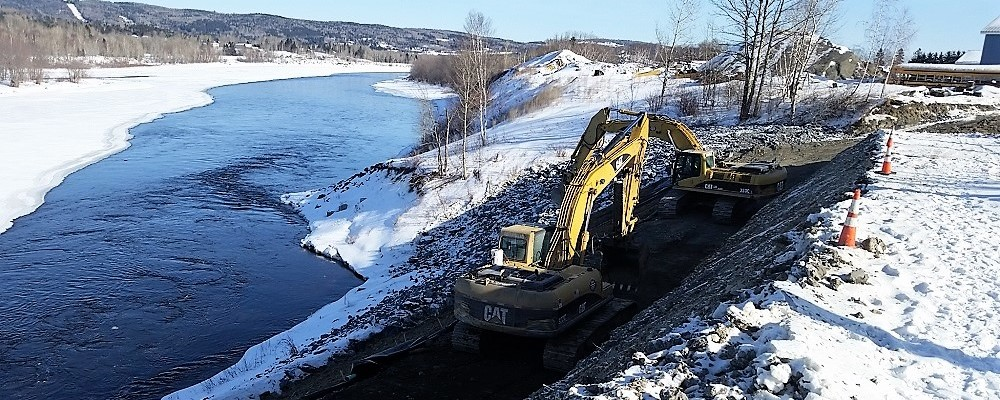 photo of excavators working on a dirt road alongside a river in winter
