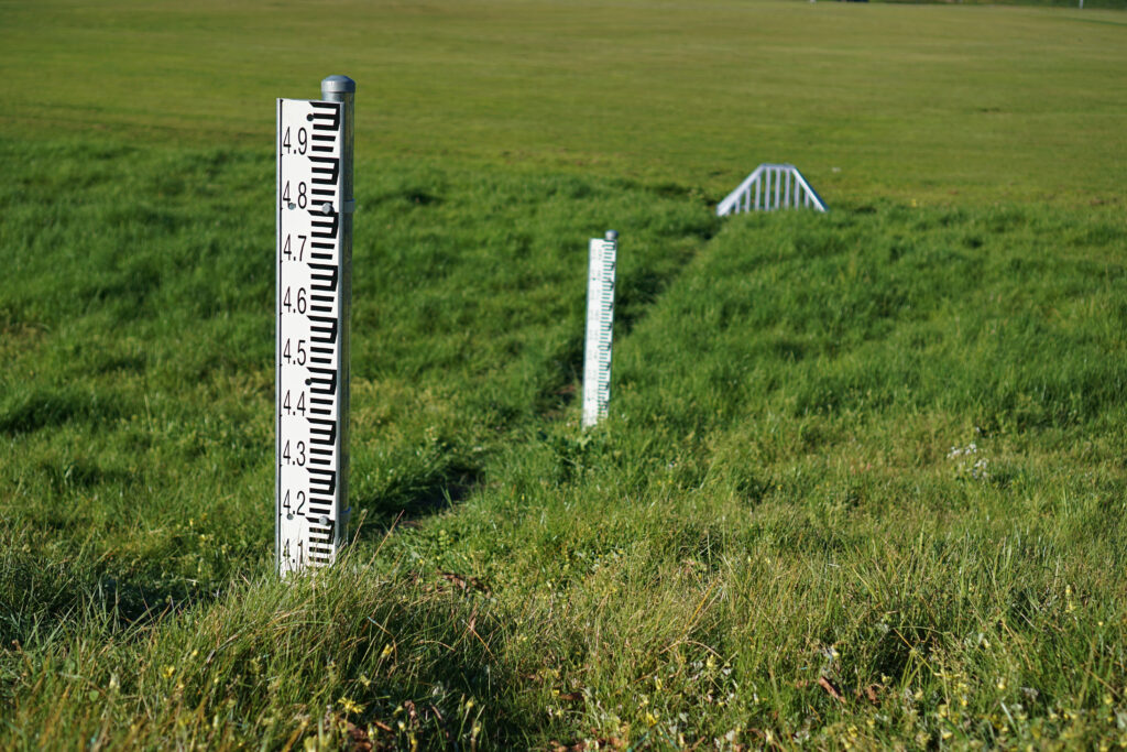 photo of industrial measuring rulers in large grassy field