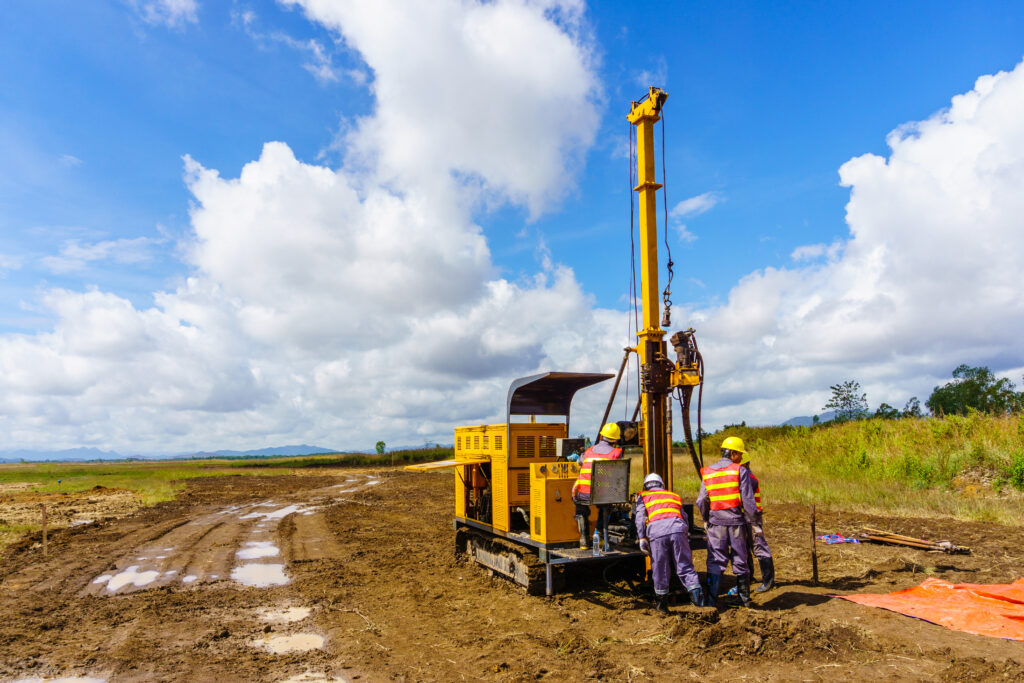 photo of four engineers working on equipment in a large field
