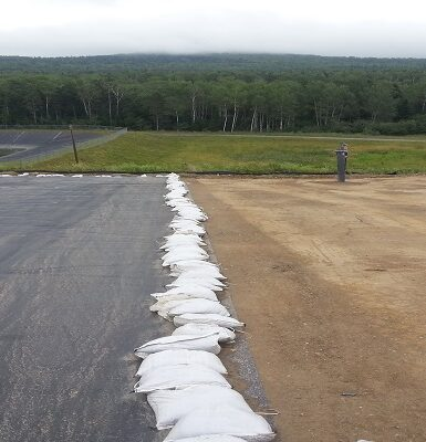 photo of a large flat area half dirt and half covered in a black tarp