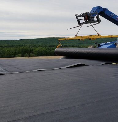 photo of work equipment and two engineers rolling out a large black tarp