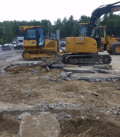photo of excavation equipment at a construction site digging up a parking lot