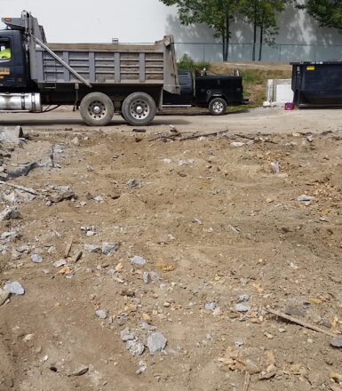 photo of a dump truck at a dirt filled construction site digging up a parking lot