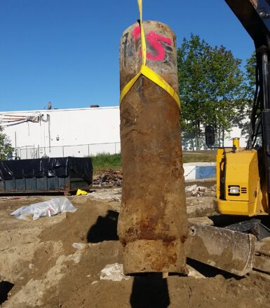 photo of an excavator removing a large cylindrical object from the ground