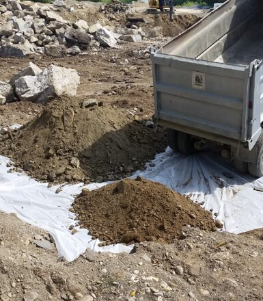 photo of a dump truck dumping a pile of dirt at a construction site