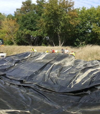 photo of engineers pulling a large black tarp along the ground