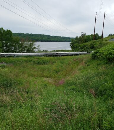 exterior photo of metal walkway power lines and river