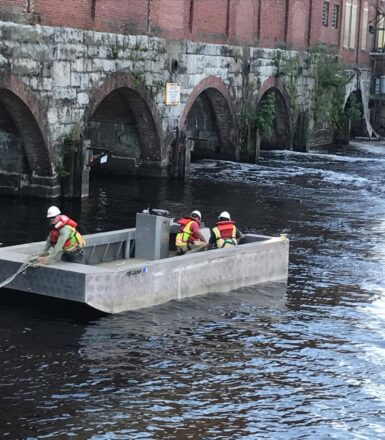 photo of three engineers in a square boat on a river next to a building