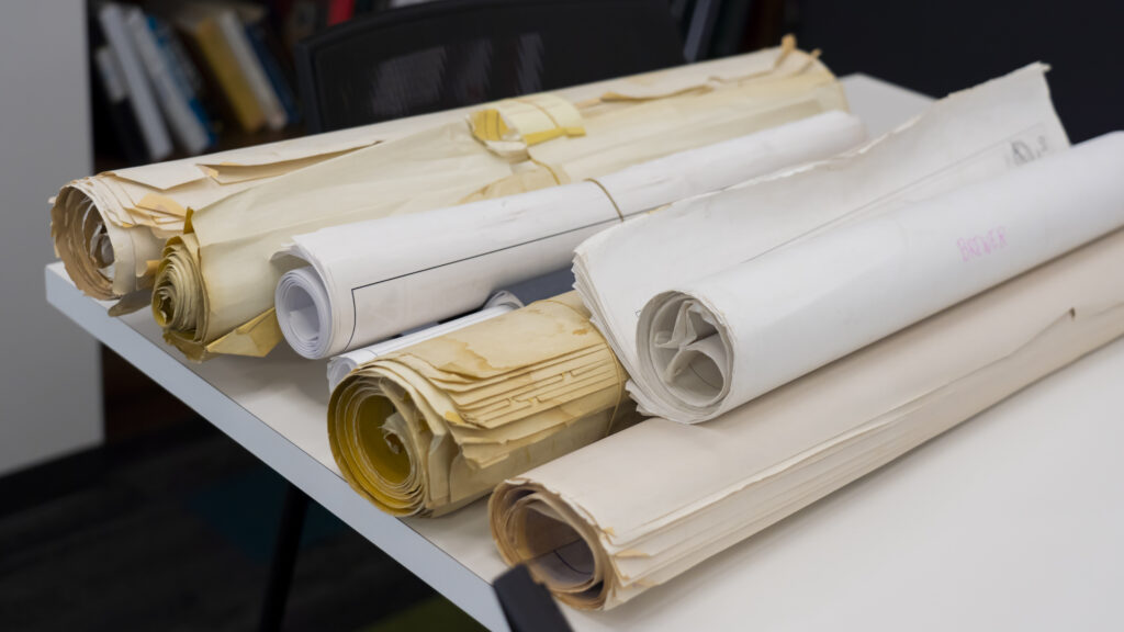 photo of large rolled up papers on table in office