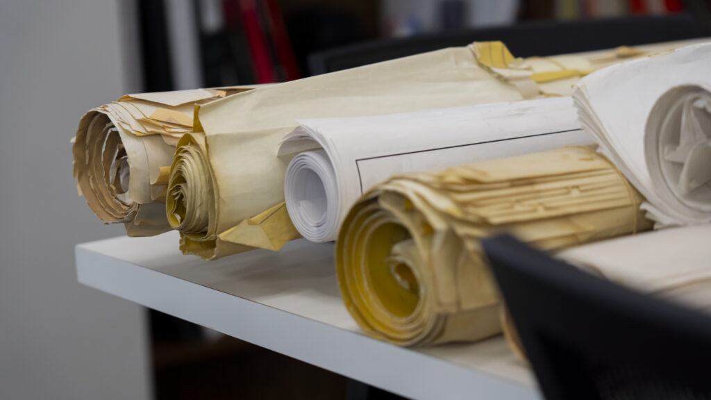 up close photo of large rolled up papers on table in office