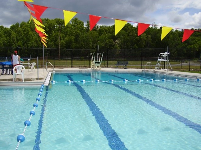 photo of a municipal swimming pool with diving board and lifeguard chair