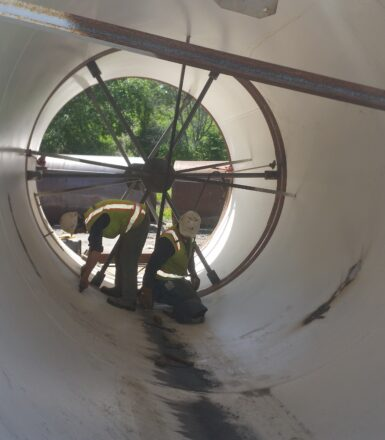 photo of two engineers working in a large pipe
